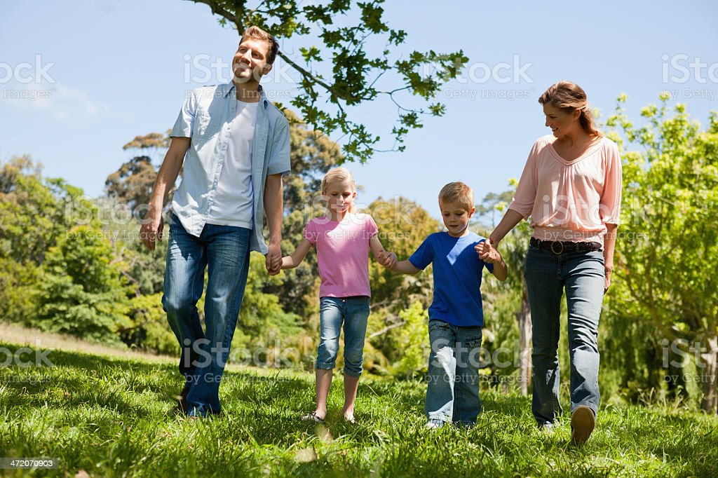 Happy family walking together in a park royalty-free stock photo