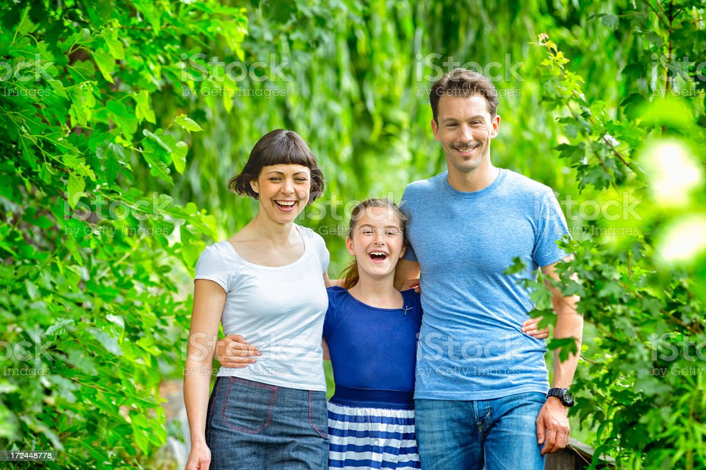 Happy family walking together in park horizontal royalty-free stock photo