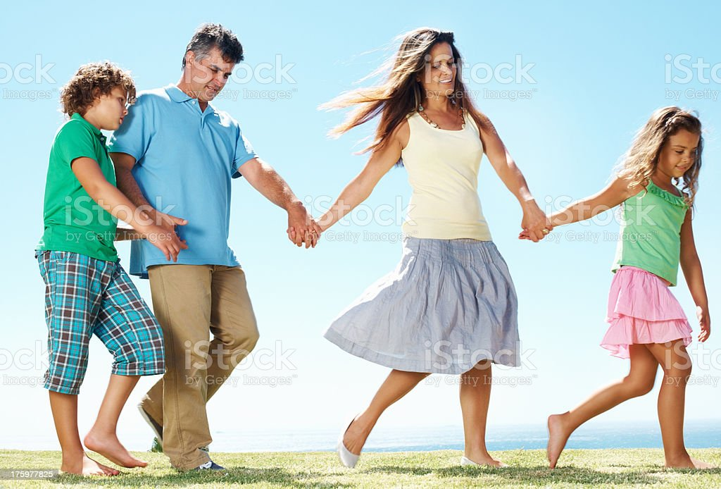 Happy family walking together in park stock photo