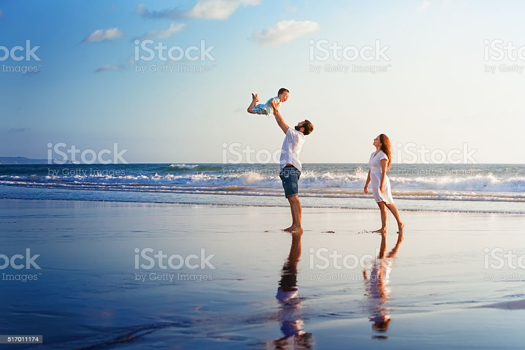 Happy family walking with fun on sunset sea beach stock photo