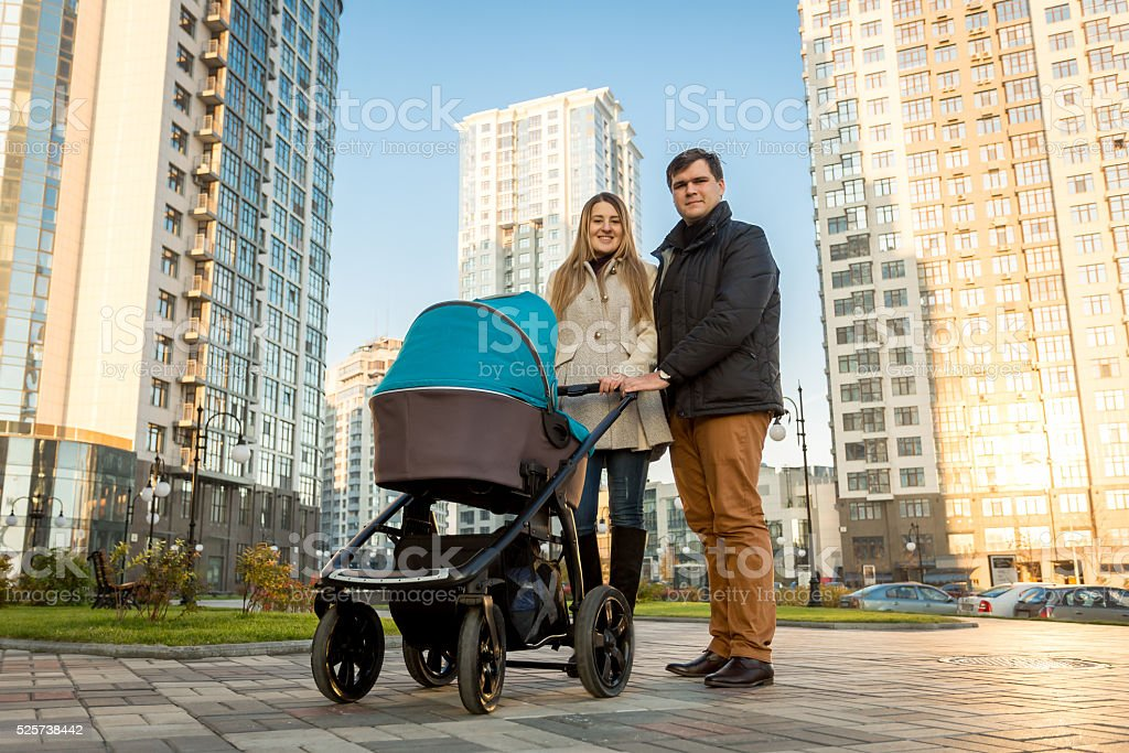 Happy family walking with pram on street at sunny day stock photo