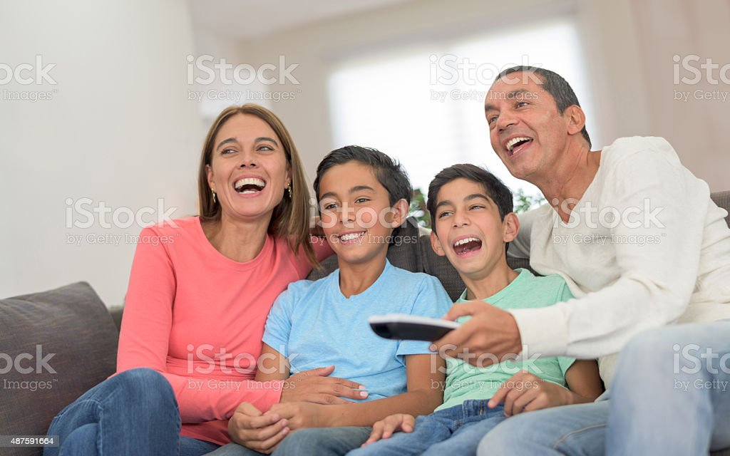 Happy family watching a movie at home stock photo