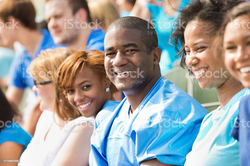 Happy family watching sporting event together in crowded stadium stock photo
