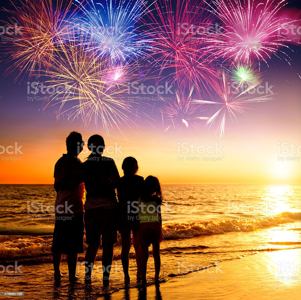 happy family watching the sunset and firework on the beach stock photo