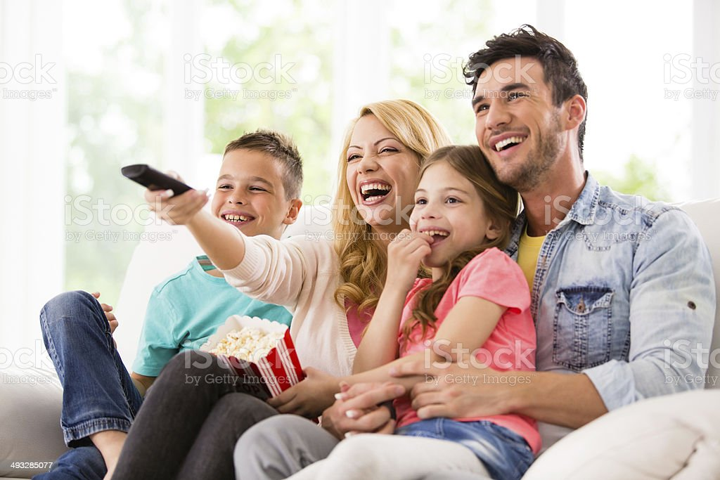 Happy family watching TV and eating popcorn stock photo