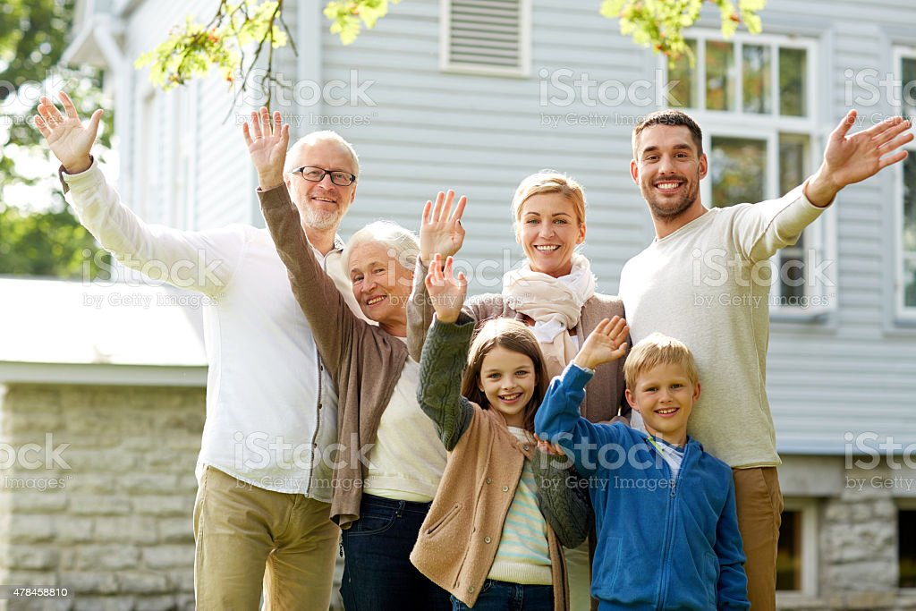 happy family waving hands in front of house stock photo