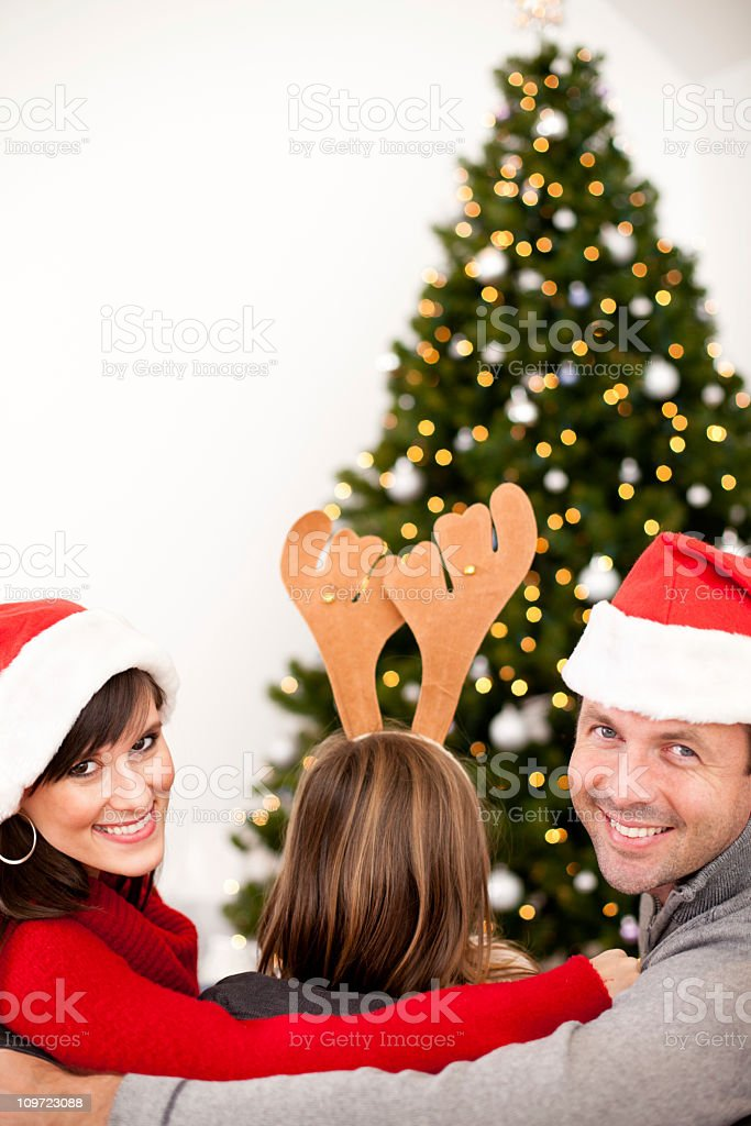 Happy Family Wearing Santa Hats and Antlers by Christmas Tree royalty-free stock photo