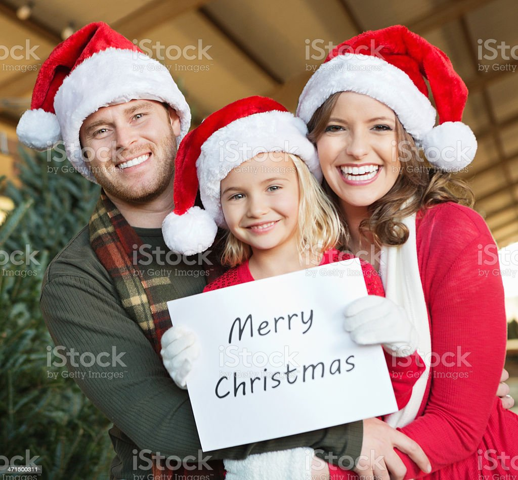 Happy family wearing santa hats and holding 'Merry Christmas: sign royalty-free stock photo