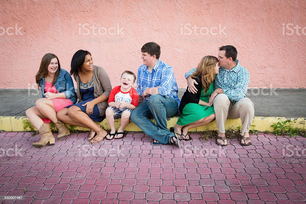 Happy Family with Adopted Daughter Sitting Together Outside stock photo