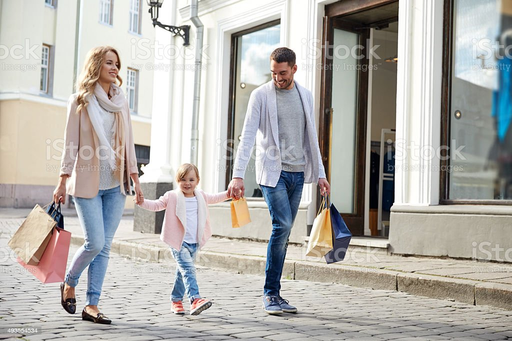 happy family with child and shopping bags in city stock photo