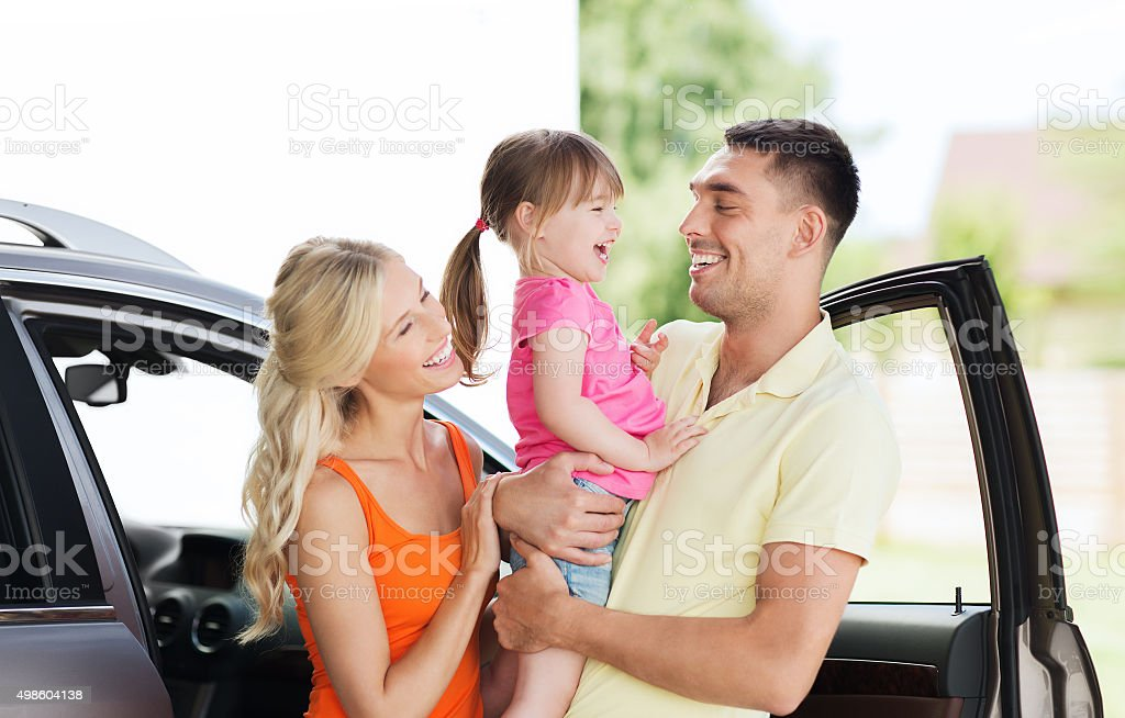 happy family with child laughing at car parking stock photo