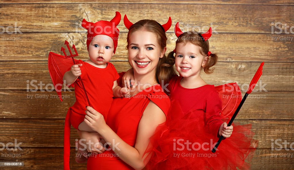 happy family with costumes devil prepares for Halloween stock photo