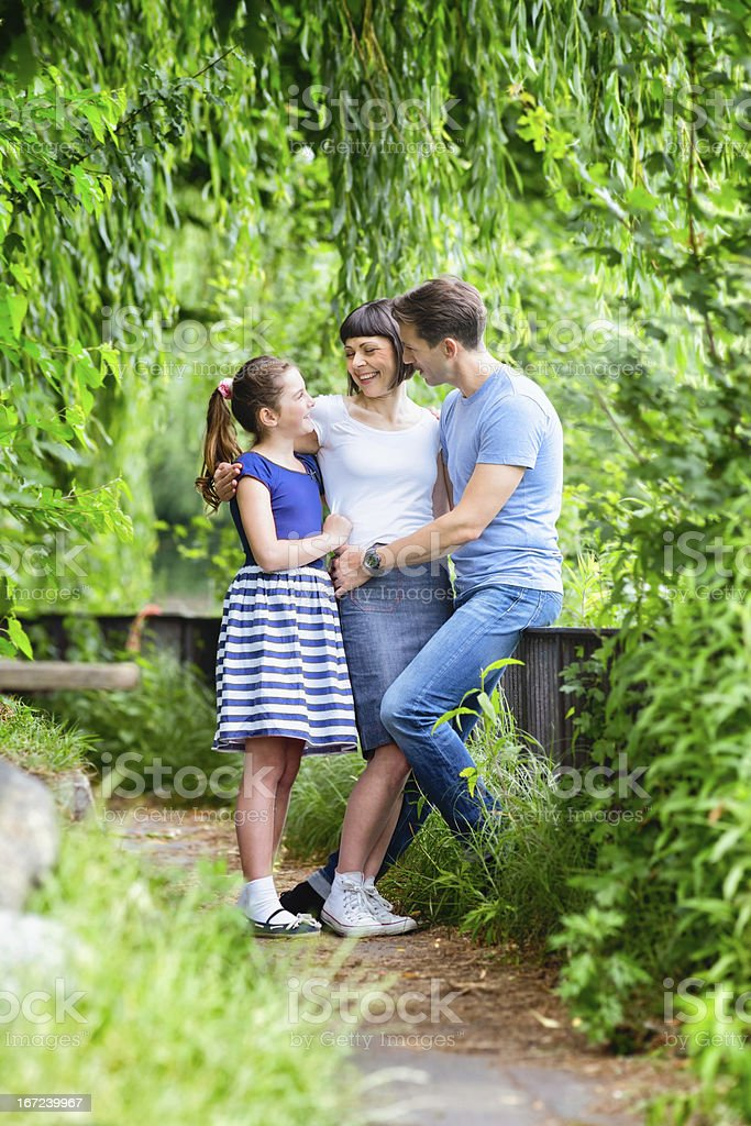 Happy family with daughter in park vertical royalty-free stock photo