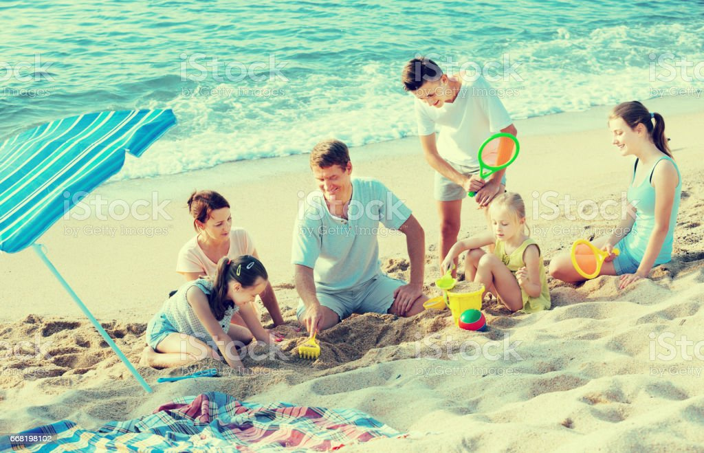 Happy family with four children playing on beach stock photo