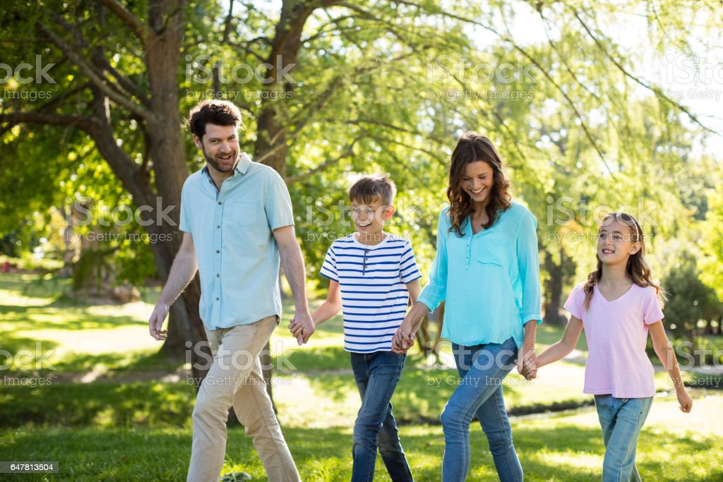 Happy family with hand in hand walking in park stock photo