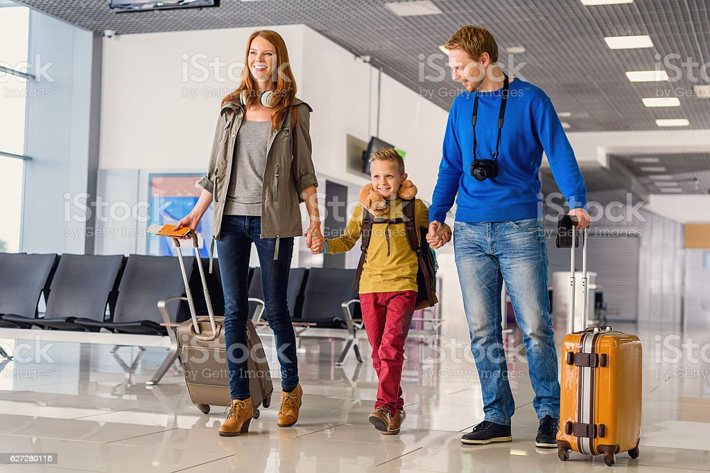 Happy family with suitcases in airport stock photo