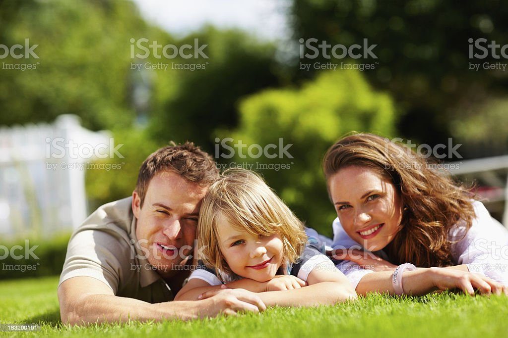 Happy family with their child lying on green grass royalty-free stock photo