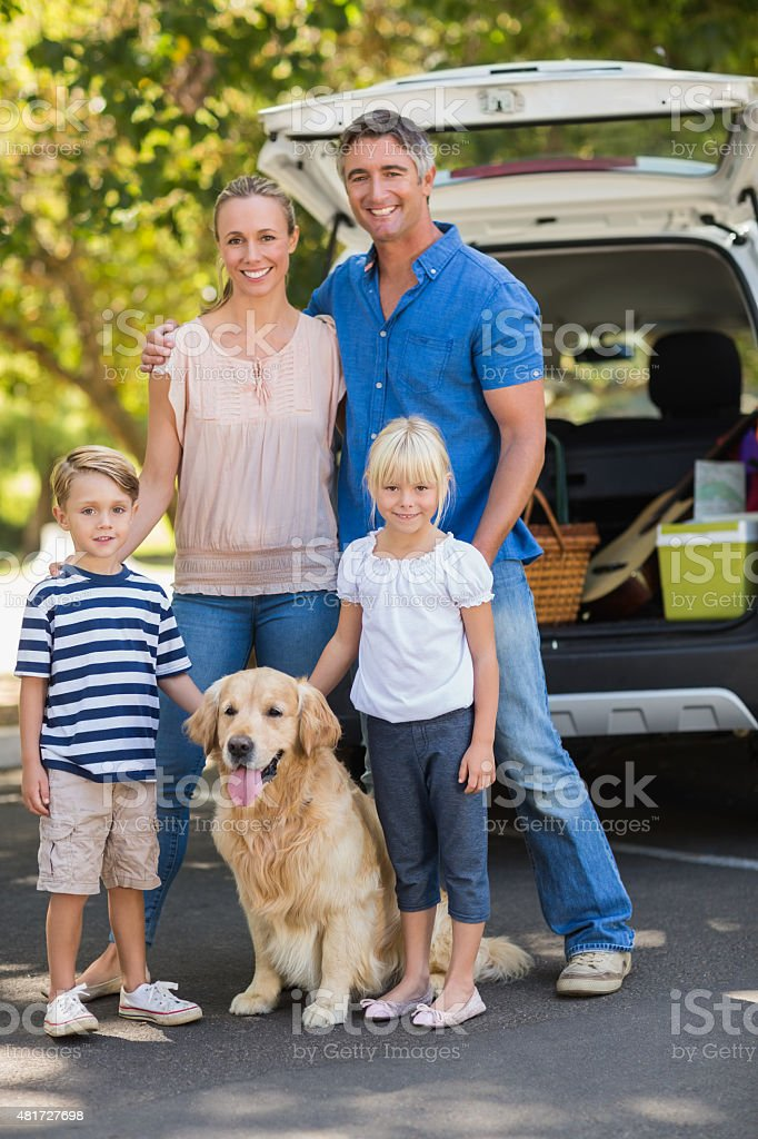 Happy family with their dog in the park stock photo