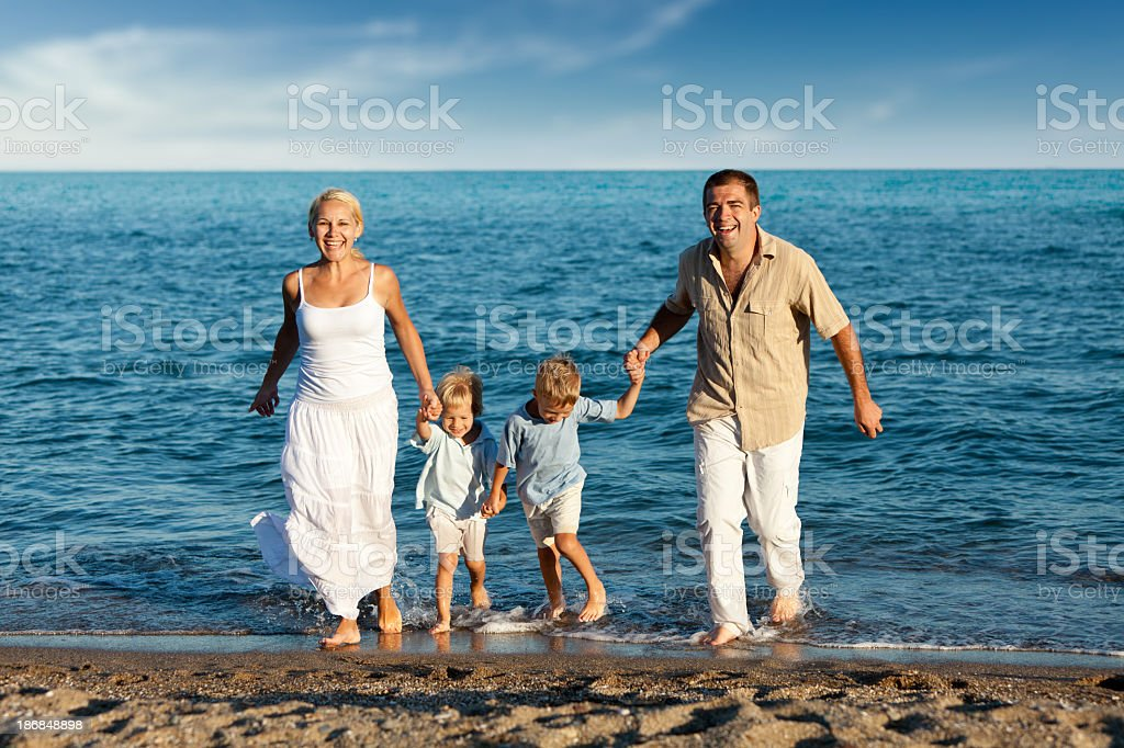 Happy family with two children running on the beach royalty-free stock photo