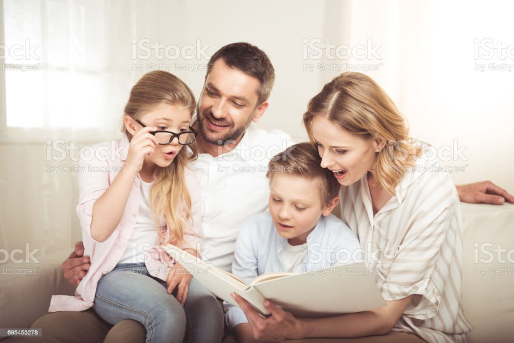 Happy family with two children sitting on sofa and reading book together stock photo