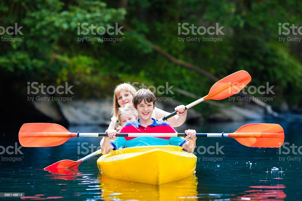 Happy family with two enjoying kayak ride on beautiful river stock photo