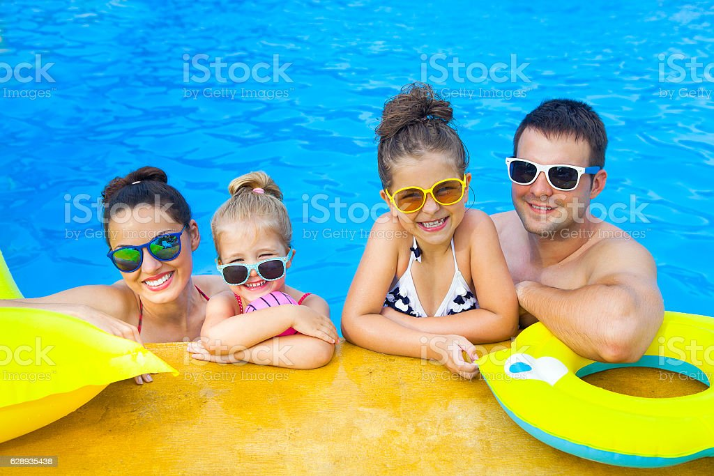 Happy family with two kids having fun in swimming pool stock photo