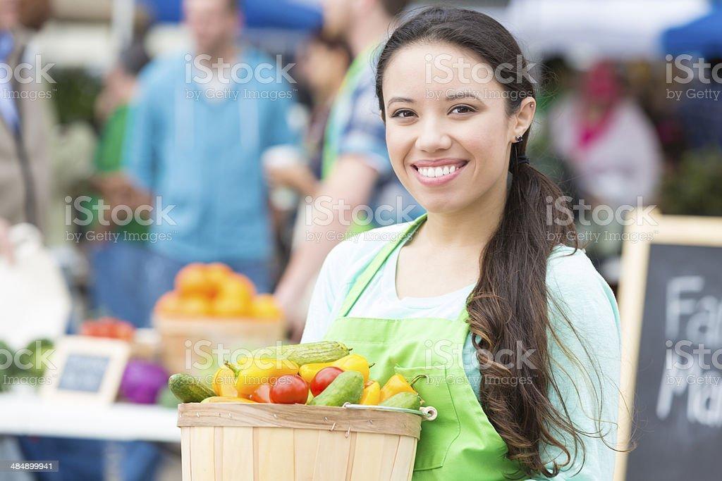 Happy farmers market vendor holding basket of fresh vegetables stock photo