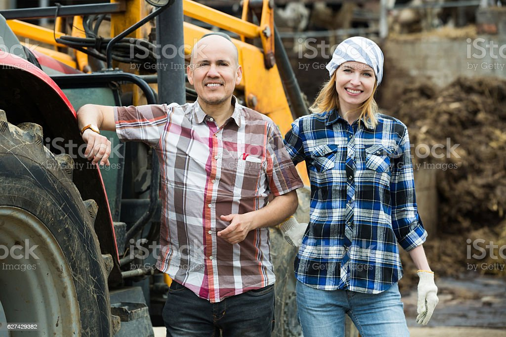Happy farmers working at machinery stock photo