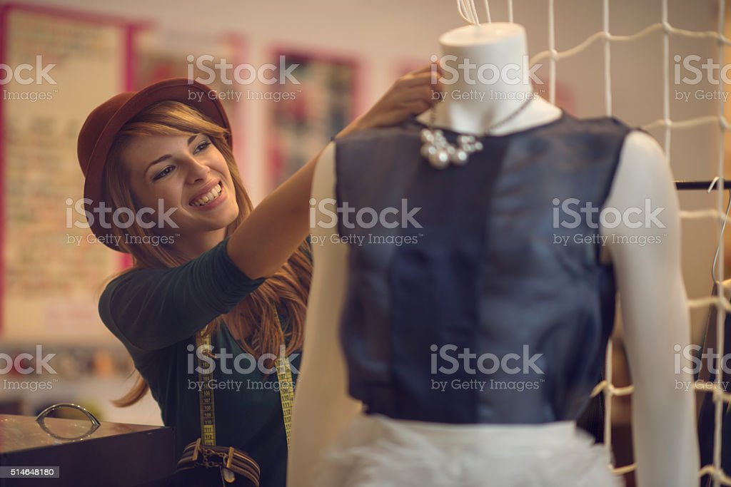 Happy fashion designer adjusting clothes on a mannequin. stock photo
