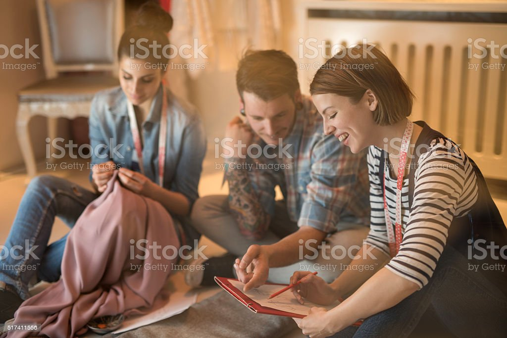 Happy fashion designer working on new designs with her colleagues. stock photo