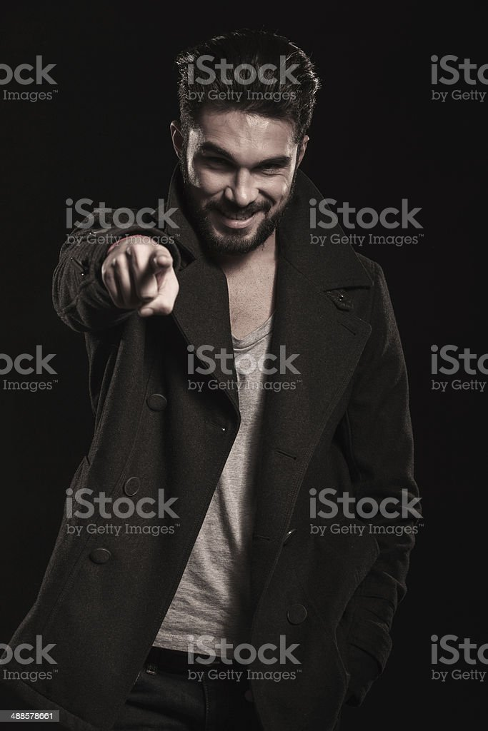happy fashion man in long coat pointing his finger stock photo