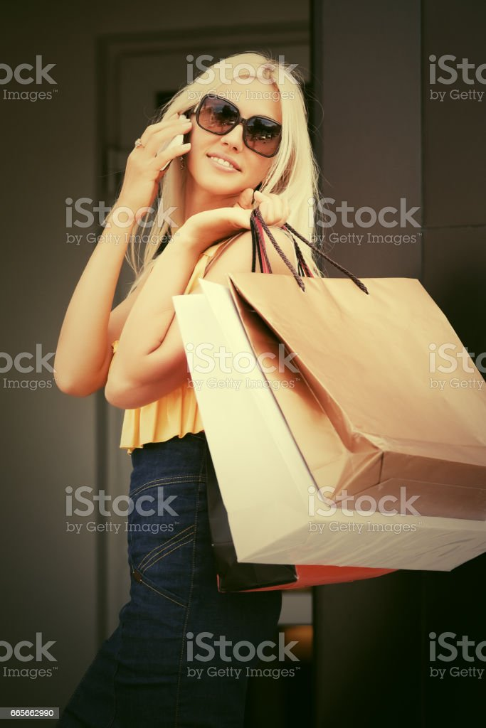 Happy fashion woman with shopping bags calling on mobile phone stock photo