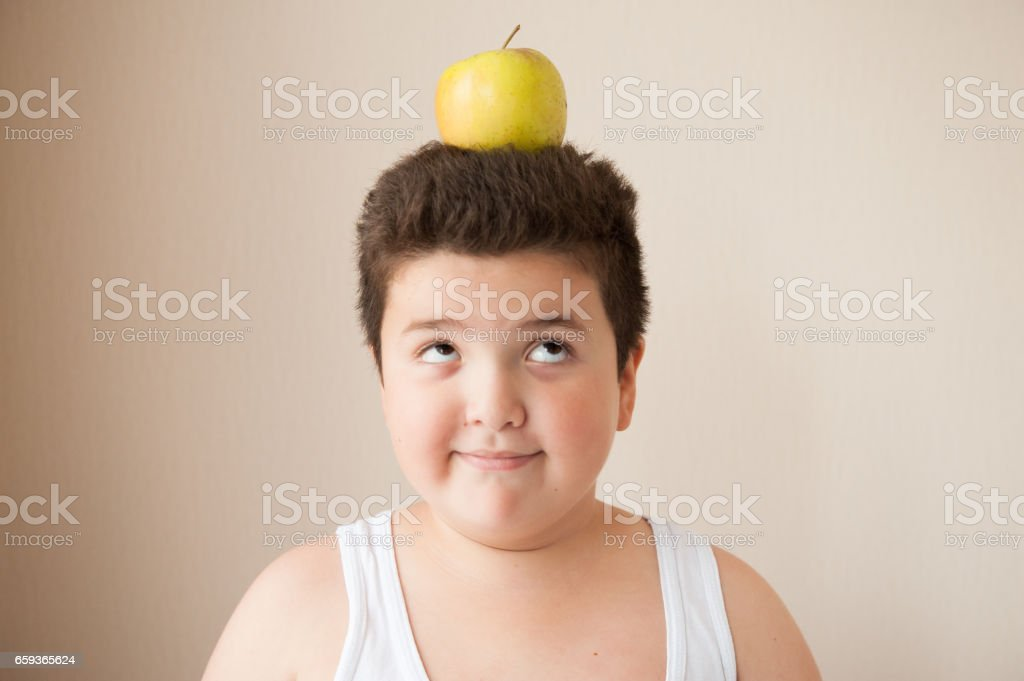 happy fat boy with an apple on his head stock photo