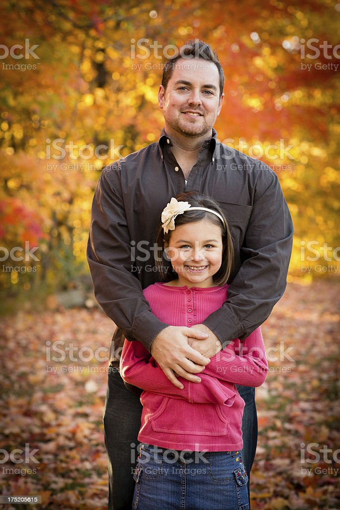 Happy Father and Daughter Cuddling Outside on Beautiful Fall Day royalty-free stock photo