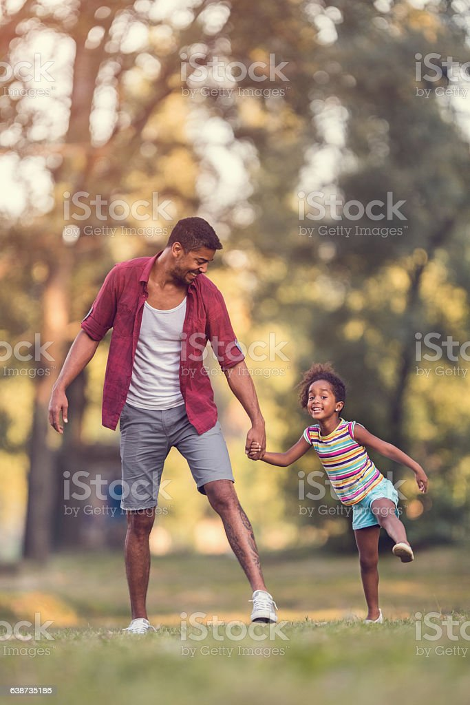 Happy father and daughter having fun in the park. stock photo