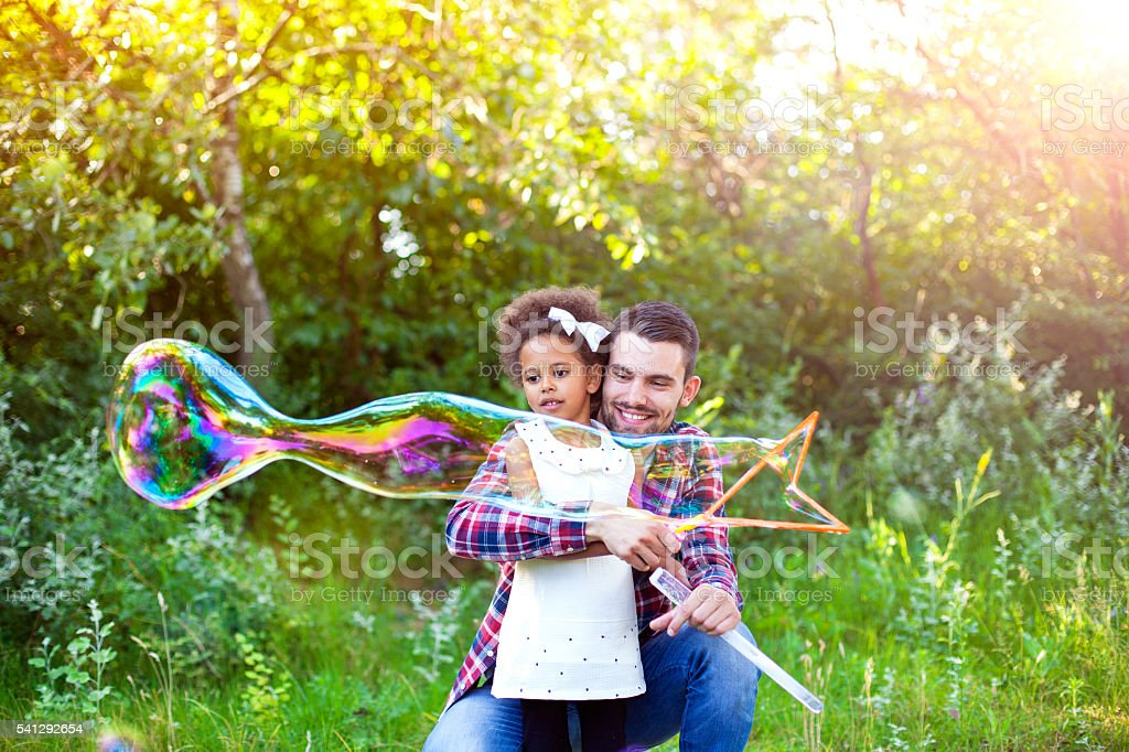 Happy father and daughter playing soap bubbles in park. stock photo