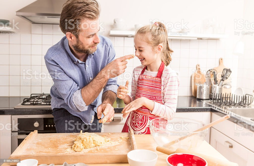 Happy father and daughter preparing cookie dough in the kitchen stock photo