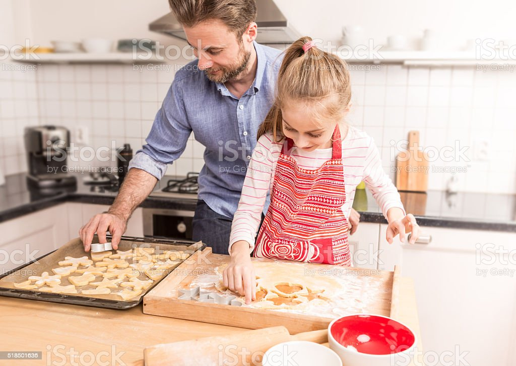 Happy father and daughter preparing cookies to bake stock photo