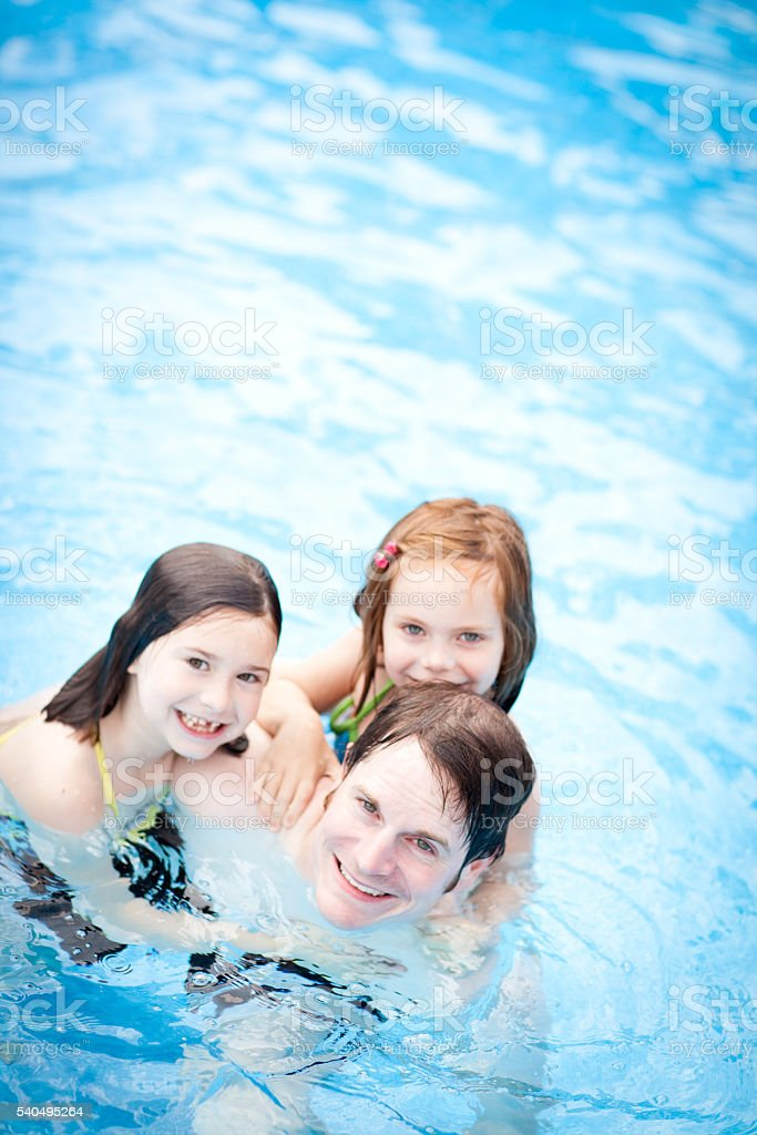 Happy Father and Daughters Together in Swimming Pool stock photo