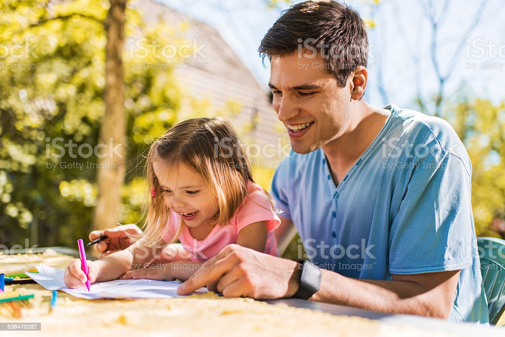 Happy father and his little girl coloring together outdoors. stock photo
