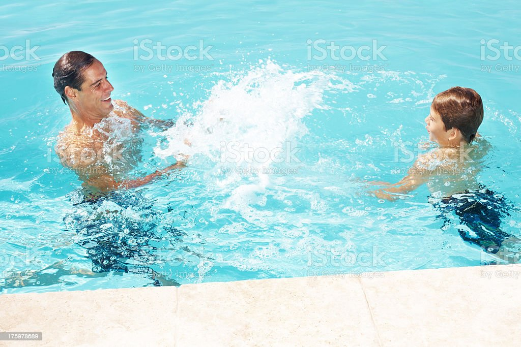 Happy father and his small son playing in pool stock photo