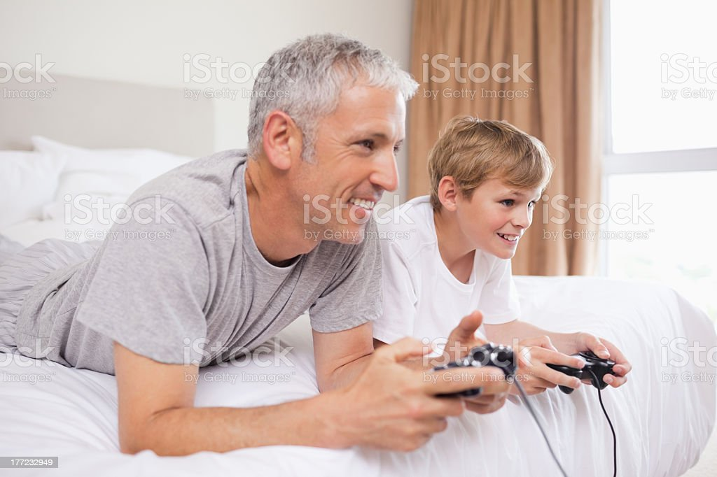 Happy father and his son playing video games royalty-free stock photo