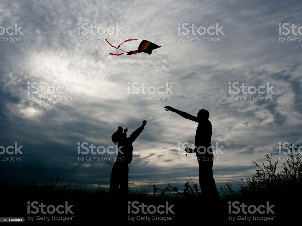 happy father and little son launching a kite at sunset stock photo