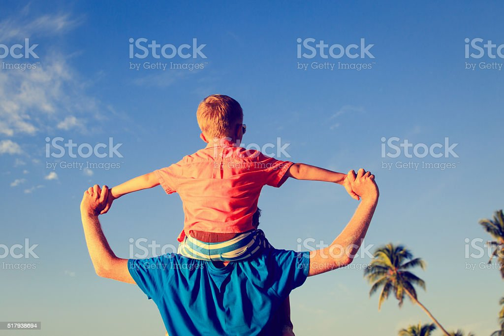 happy father and little son play on sky at beach stock photo