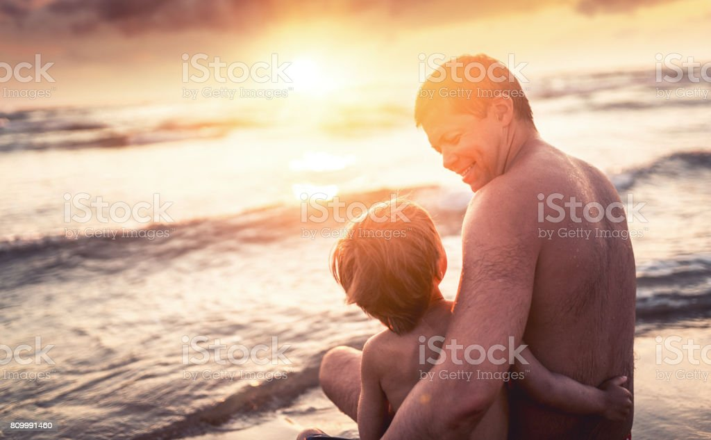 Happy father and son enjoying sea at sunset stock photo