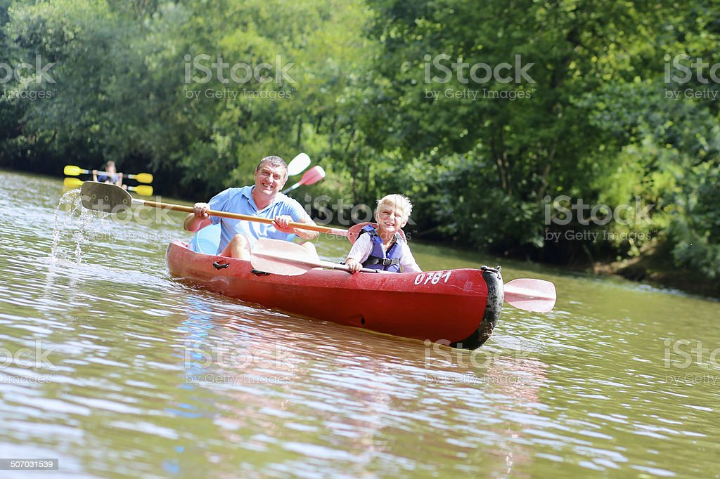 Happy father and son kayaking on the river stock photo