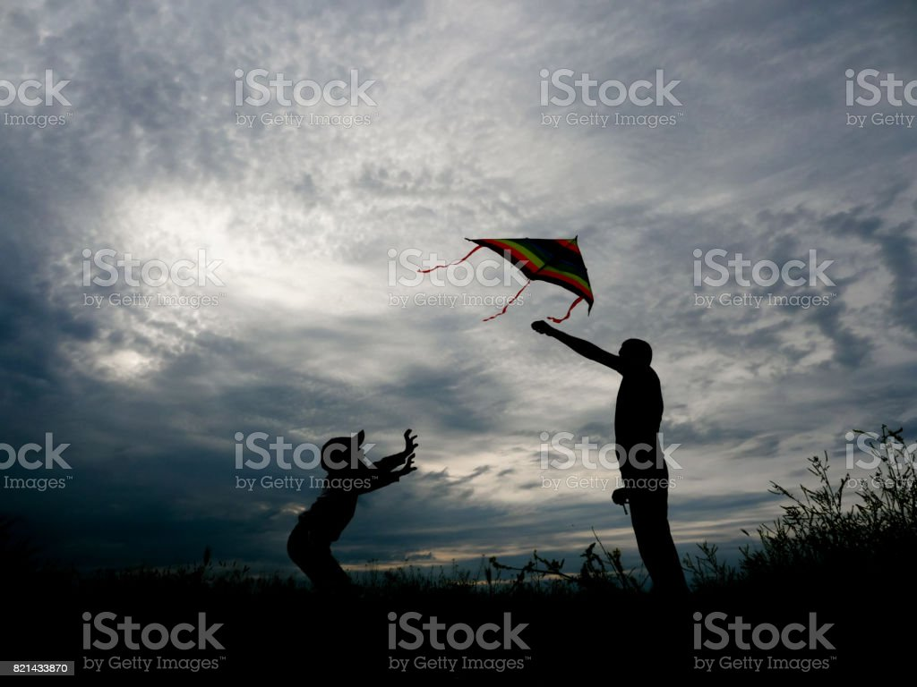 happy father and son launching a kite at sunset stock photo