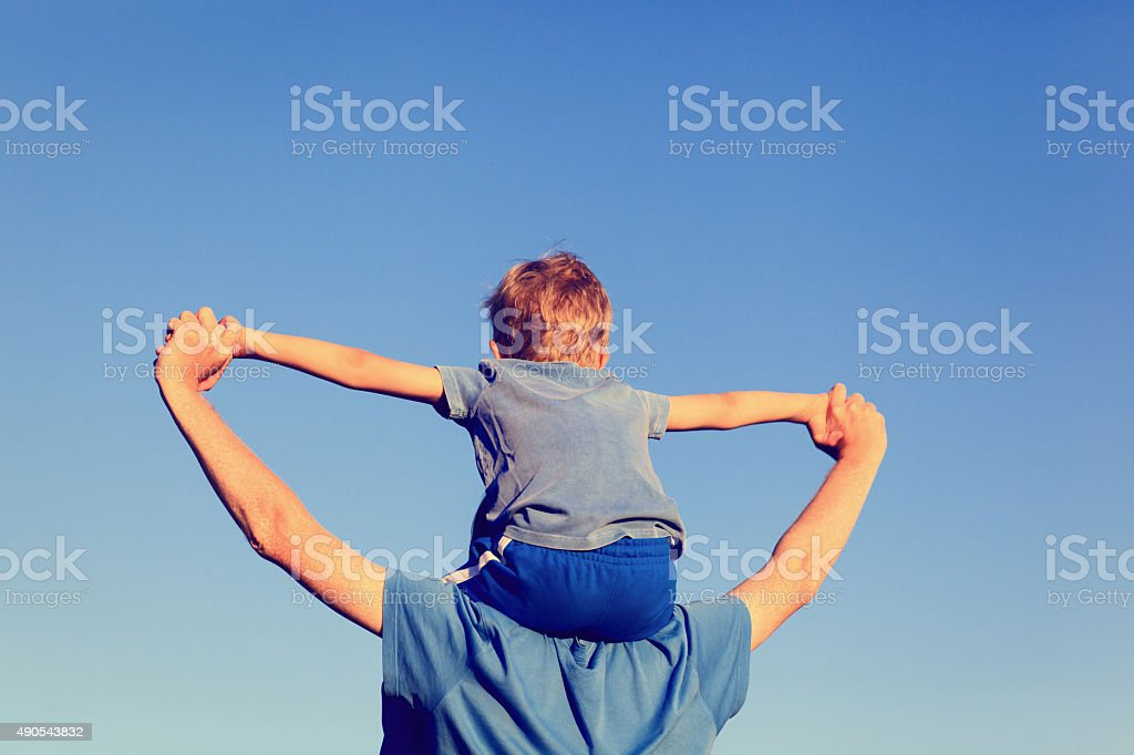 happy father and son on shoulders play at sky stock photo