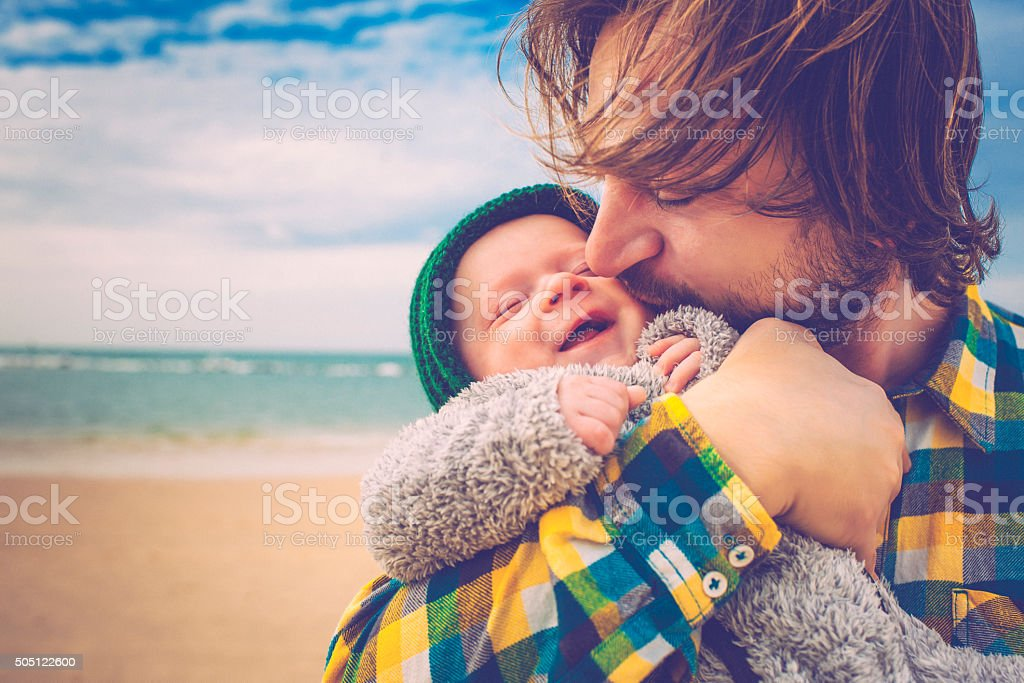 Happy father and his baby son having fun on the beach