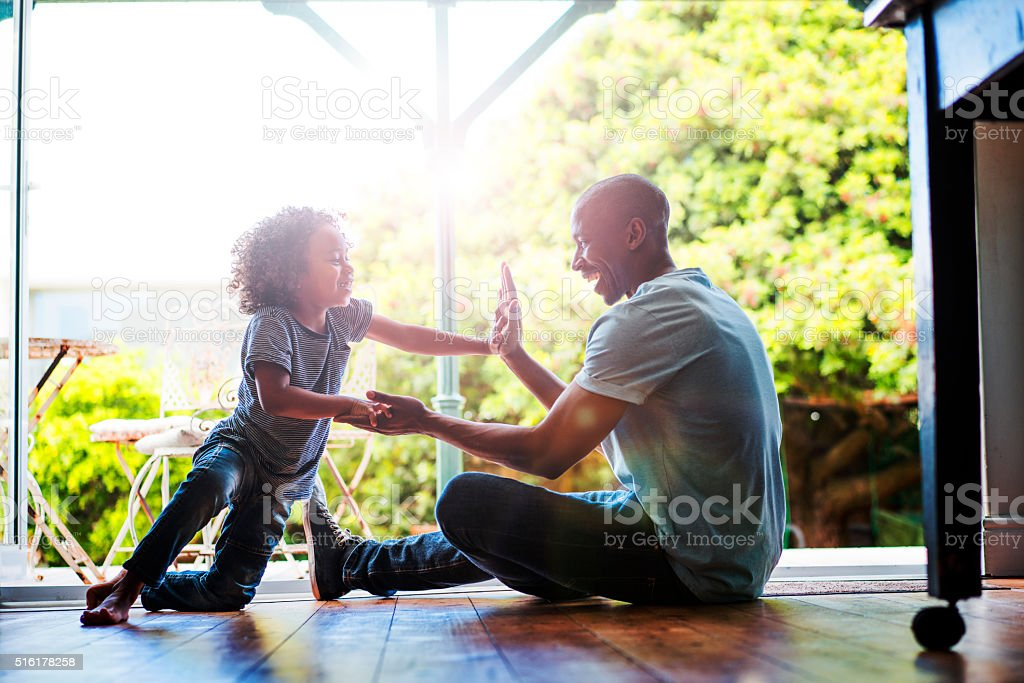 Happy father and son playing on floor at home stock photo